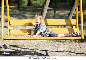 Funny little boy posing on a swing in the park