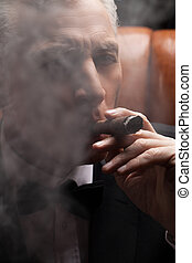 Through a cigar smoke. Close-up of confident mature man...