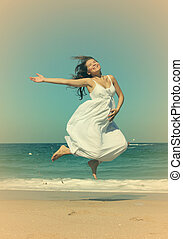 beautiful pregnant woman jumping on the beach. Photo in old...