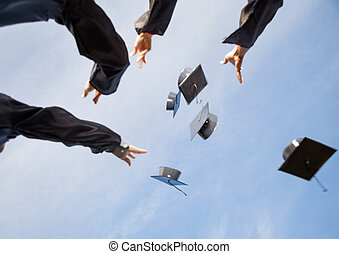 Students Throwing Mortar Boards In Air Against Sky -...