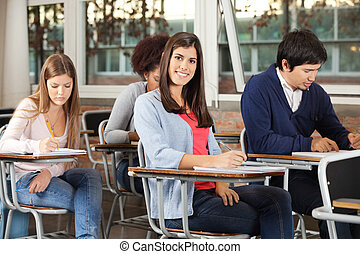 Woman With Students Writing Exam In Classroom