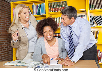 Student With Teachers Looking At Each Other In Library -...