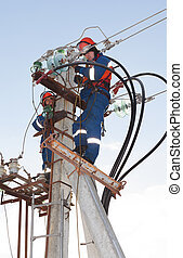 Electricians in blue overalls working at height on a support...