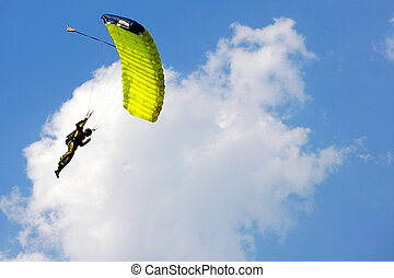 Parachuter descending with a parachute against blue sky