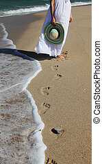Young woman in white dress walking at the beach. Focus on...