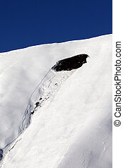 Trace of avalanche on off piste slope in sun day. Close-up view. Ski resort Gudauri. Caucasus Mountains, Georgia.