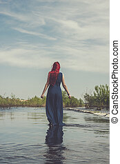 red-haired woman walking in the river shallow water