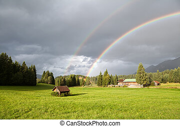 colorful rainbow during rain in Alps, Bavaria, Germany