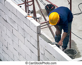 Build a wall - Construction worker is building a wall using...