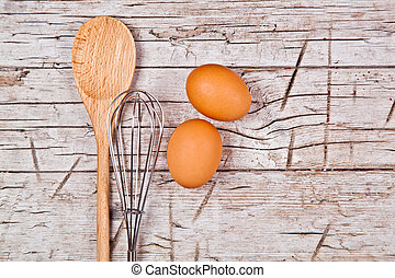 spoon, wire whisk and two brown eggs