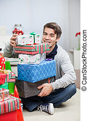 Man With Stack Of Christmas Presents At Home