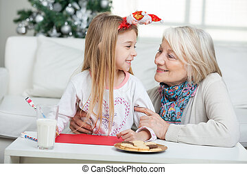 Grandmother And Girl With Cardpaper Looking At Each Other -...