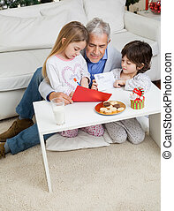 Man Assisting Children In Making Christmas Greeting Card
