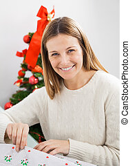 Happy Woman Wrapping Christmas Present - Portrait of happy...