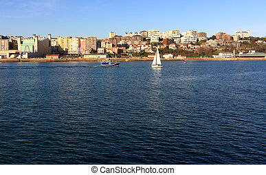 small sailboat white sailing in front of the city of Santander, Spain