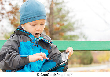 Cute little boy surfing on a tablet computer warmly dressed...