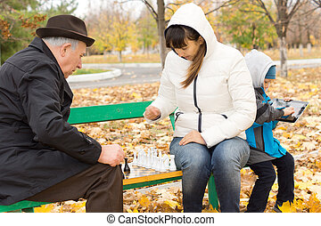 Attractive woman playing chess with an elderly man