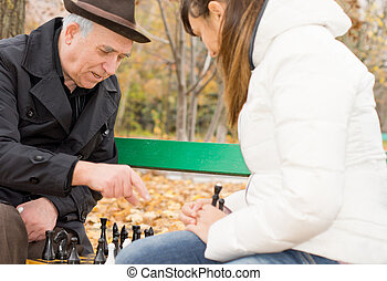 Senior man playing chess with his granddaughter