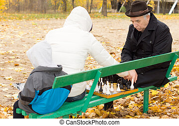 Grandfather playing chess with his daughter