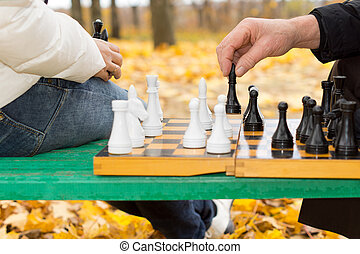 Elderly man making a chess move - Close up of the hands of...