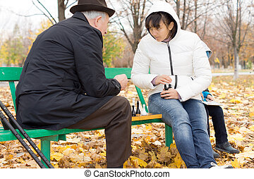 Two friends playing chess in the park