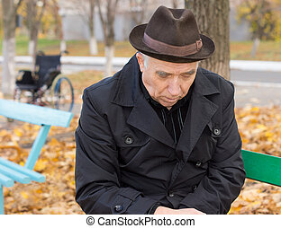 Sad lonely old man on a park bench - Close up portrait of a...