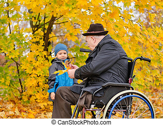 Elderly disabled man playing with his grandson - Elderly...
