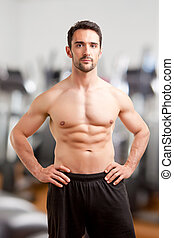 Fit Man Standing With Arms At His Waist in a Gym - Fit man...