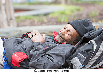 Old african american homeless man sleeping outside during...