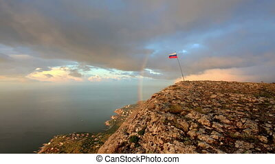 4K. Russian flag on the top of a mountain on the background...