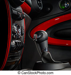Gear shift handle in modern sport car. Red and black.