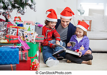 Siblings And Father Reading Book By Christmas Presents -...