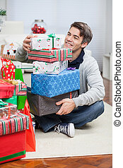 Smiling Man With Stack Of Christmas Gifts