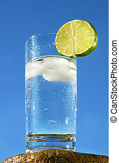Cold glass of water against a blue sky