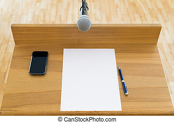Microphone at the speech podium Mobile phone, documents, pen...