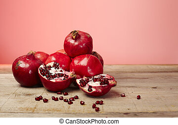 Red pomegranate fruit seeds on a wooden table
