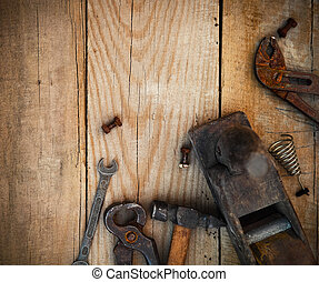 Dirty set of hand tools on a wooden background