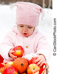 Happy smiling baby with apple in winter day