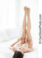 Wearing pantyhose. Beautiful young women in lingerie wearing...
