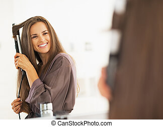 Smiling woman curling hair with straightener