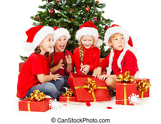 Christmas kids in red Santa hat with presents sitting under...