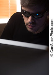 Computer hacking. Confident young men in glasses working at...