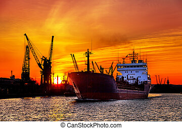 Silhouette of sea port cranes over sunset - Ship and cranes...