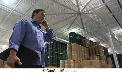 Warehouse Supervisor 2 - A supervisor talks on his phone in...