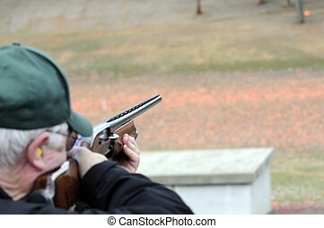 Trap shooting - Trap shooter taking aim on a clay bird