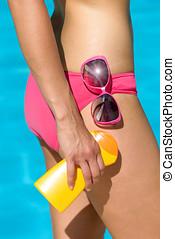 Skin care and sun protection on summer before sunbathing or swimming. Suntan lotion or sunscreen, sunglasses and approving hand gesture with thumbs up. Woman in bikini.