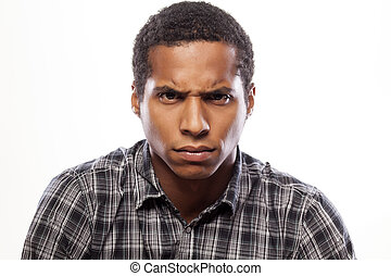 scowling young man - somber dark-skinned young man poses...