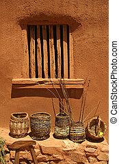 Baskets against an adobe wall.