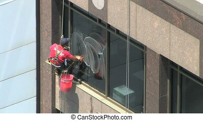 Window Washer - Man washes windows on a skyscraper, high...