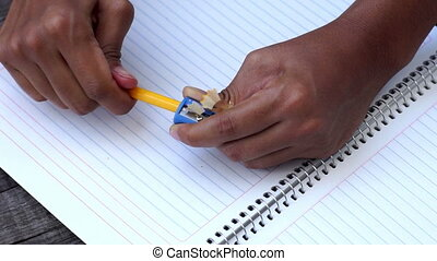 Person sharpens a pencil - A person sharpens a pencil